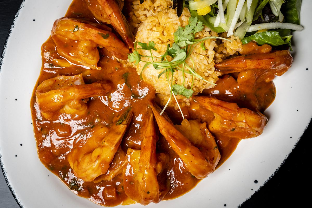 A close-up photo of prawns covered in sauce with yellow rice