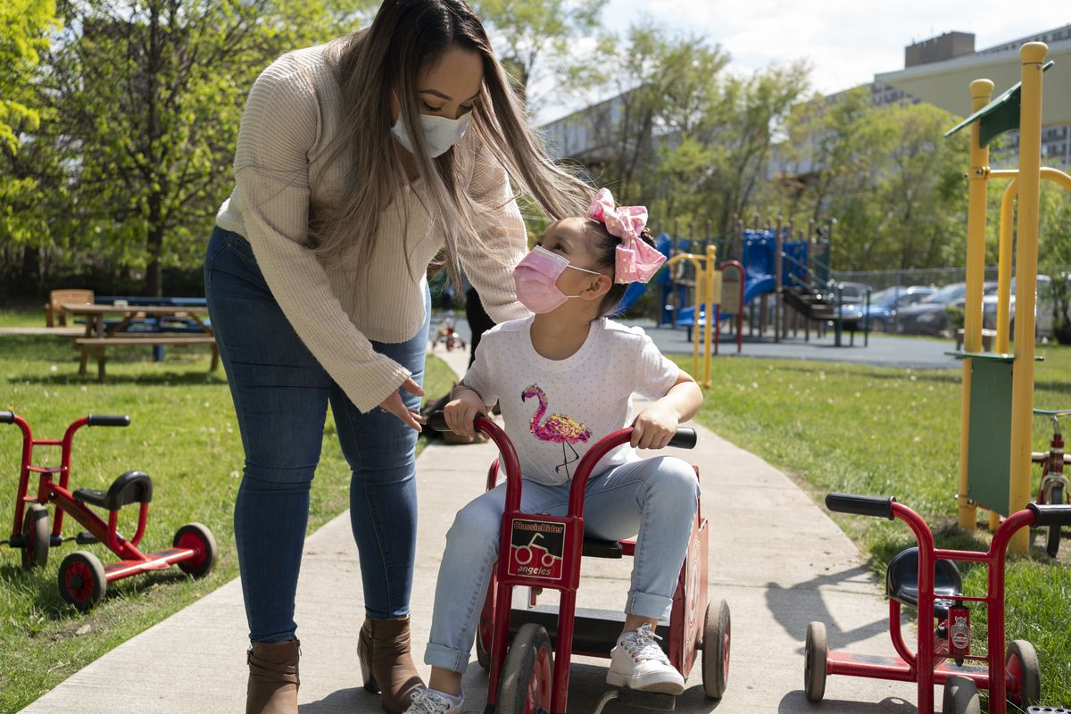A mother wearing jeans, tan shirt and protective mask pushes her daughter on a red tricycle. The daughter is wearing a white flamingo shirt, pink mask, pink bow and jeans.