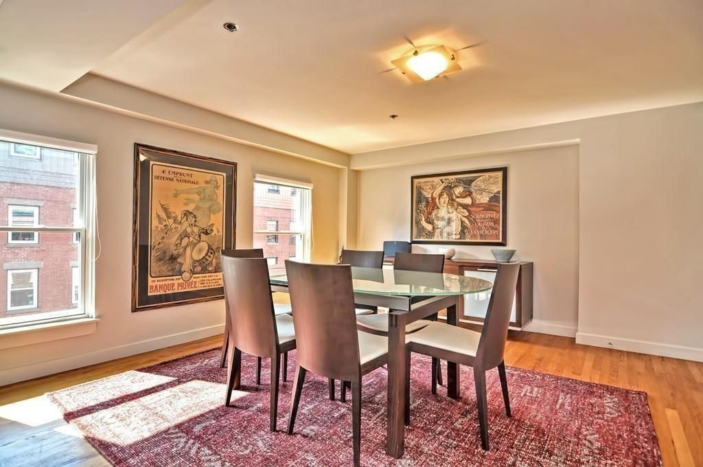 A spacious dining room with a table and six chairs.