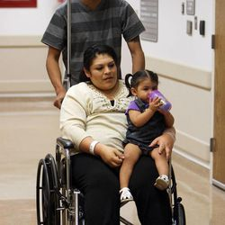 Guillermina Garcia is pushed in a wheelchair by her husband, Fernando, as she holds her daughter, Julietta, prior to speaking to the media about their quintuplets delivered at University of Utah Health Care in Salt Lake City on Tuesday, May 28, 2013.