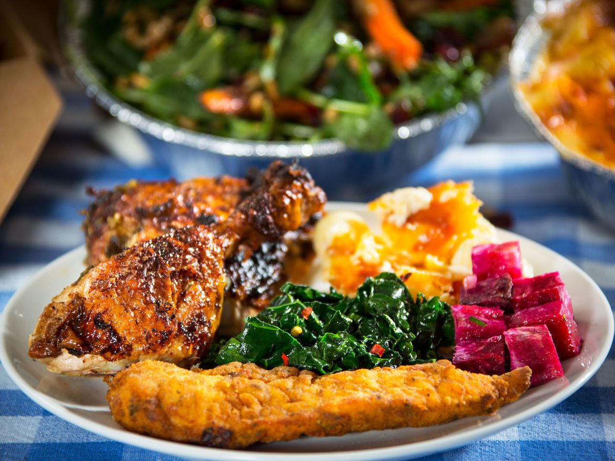 A bright plate with fried chicken, fried fish, stewed greens, and mashed potatoes, with takeout dishes blurred in the background on a colorful textured tablecloth