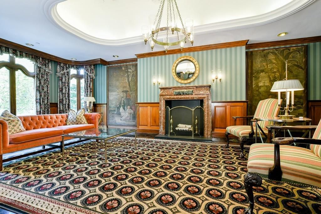 An expansive living room with a large marble fireplace and a couch facing two chairs across a strikingly ornate carpet.