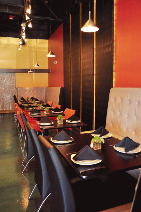 A restaurant interior depicting red and black walls and several tables against a wall