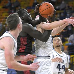 San Diego State forward Aguek Arop, center left, fights for a rebound against Utah State guard Brock Miller during the second half of an NCAA college basketball game Thursday, Jan. 14, 2021, in Logan, Utah.