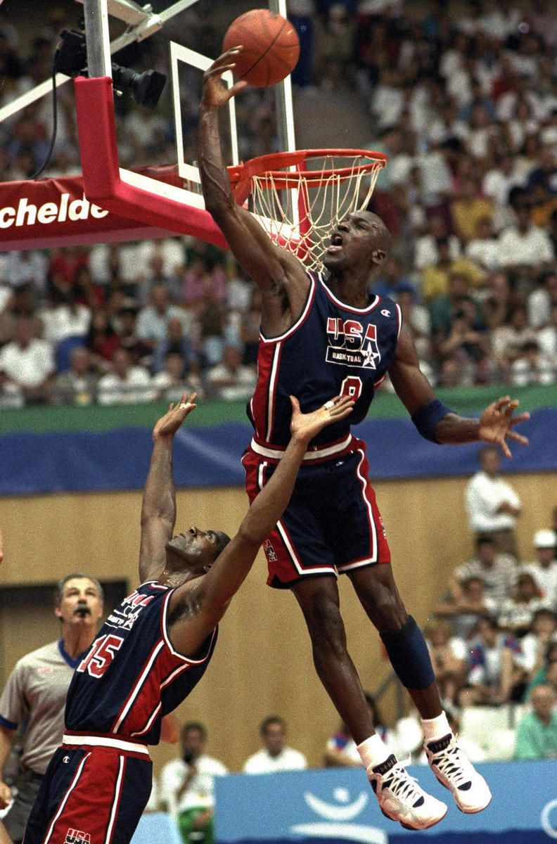 In this July 27, 1992, file photo, USA's Michael Jordan sails high above teammate Magic Johnson knocking away a shot during the first half of their preliminary round basketball game with Croatia at the Summer Olympics in Barcelona.