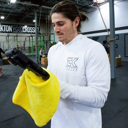 Trainer Josh Sturges cleans a tablet he uses during a group workout following a session at Tekton Fitness in Murray on Friday, March 13, 2020. Gym patrons began cleaning equipment with Clorox and were instructed to clean their hands before and after classes as part of the precautions the gym is taking during the coronavirus pandemic. Instead of signing in on tablets when they arrive, they were also instructed to sign in on their personal devices before arriving to class.