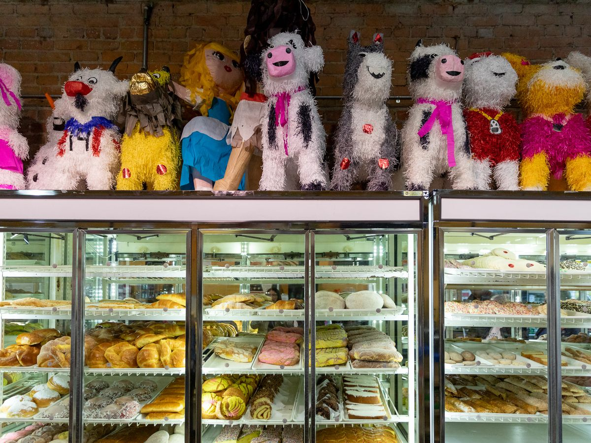 Pastry cases topped with a row of pinatas.