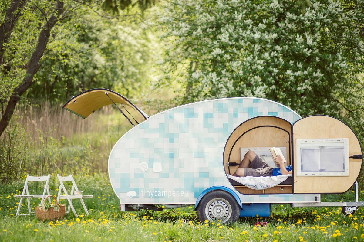 A camper trailer in a field of wildflowers. The trailer has a blue and white pattern. There is a man lounging on a bed inside the trailer. There are two chairs and a picnic basket sitting next to the trailer.