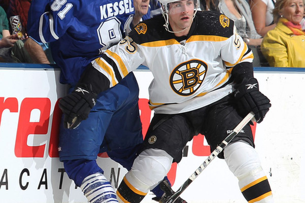 TORONTO,ON - APRIL 3:  Johnny Boychuk #55 of the Boston Bruins hammers Phil Kessel #81 of the Toronto Maple Leafs into the boards in a game on April 3, 2010 at the Air Canada Centre in Toronto, Ontario. (Photo by Claus Andersen/Getty Images)