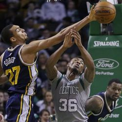 Utah Jazz center Rudy Gobert (27) taps a loose ball away from Boston Celtics guard Marcus Smart (36) during the second half of an NBA basketball game in Boston, Wednesday, March 4, 2015. The Celtics won 85-84. (AP Photo/Elise Amendola)