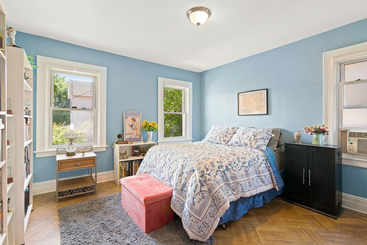 A bedroom with a medium-sized bed, light blue walls, three windows, base moldings, and hardwood floors.