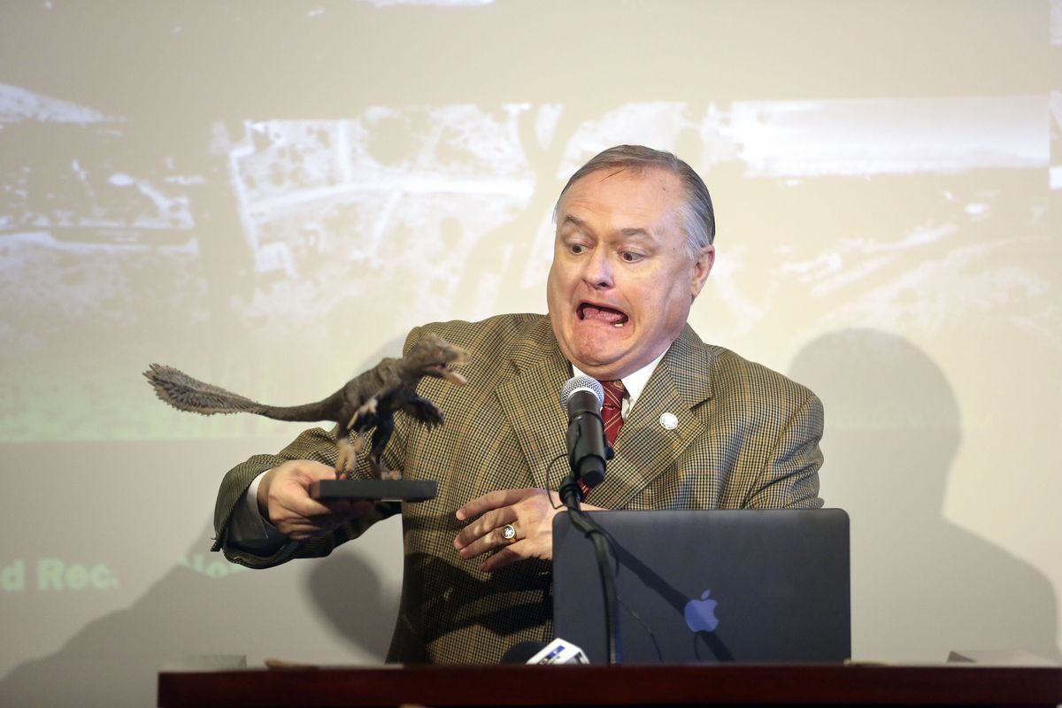 Mike Mower, Gov. Gary Herbert's deputy chief of staff, holds a statue of a Utahraptor during a press conference at the Capitol in Salt Lake City on Friday, Feb. 14, 2020, to discuss HB322, which would create Utahraptor State Park in the Dalton Wells area near Moab.