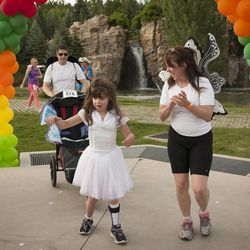 JulieLynn Reardon crosses the finish line during the Fairy Tale 5K with the help of her parents, Joe Reardon and Anita Reardon, at Thanksgiving Point in Lehi Saturday, June 21, 2014. In spite of being diagnosed with a severe form of epilepsy, JulieLynn Reardon is on grade level in most subjects.