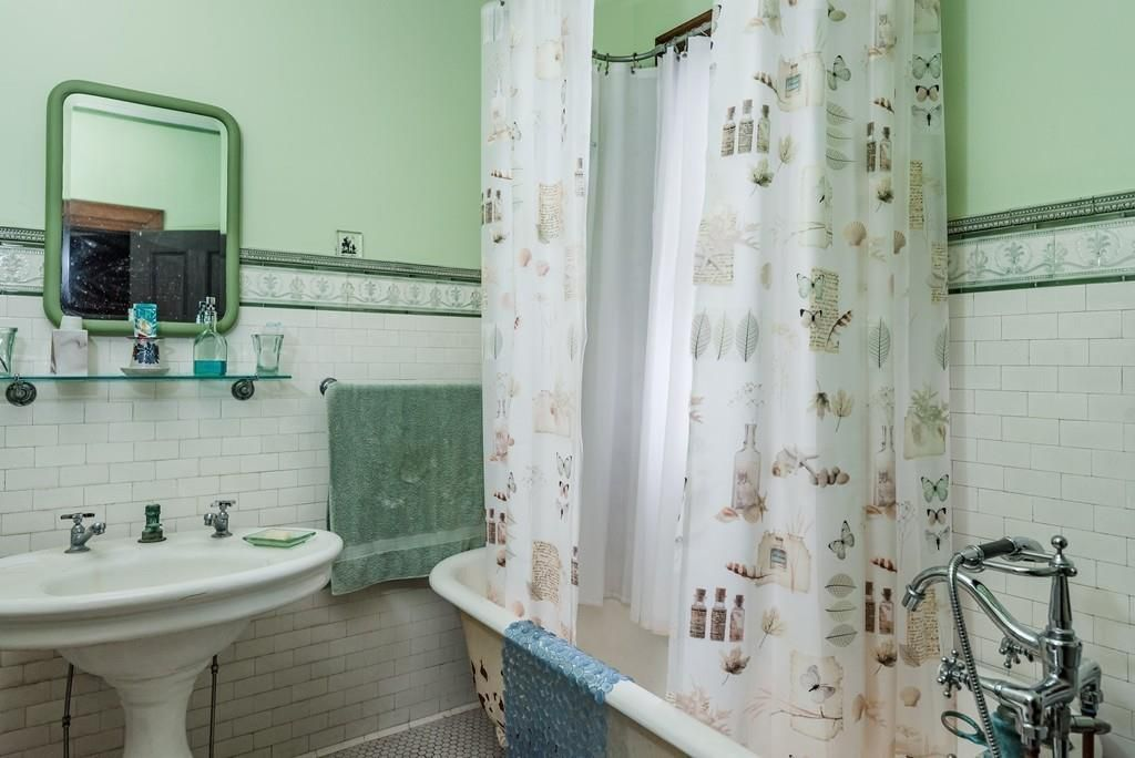 A small bathroom with a tub with a shower curtain around it.