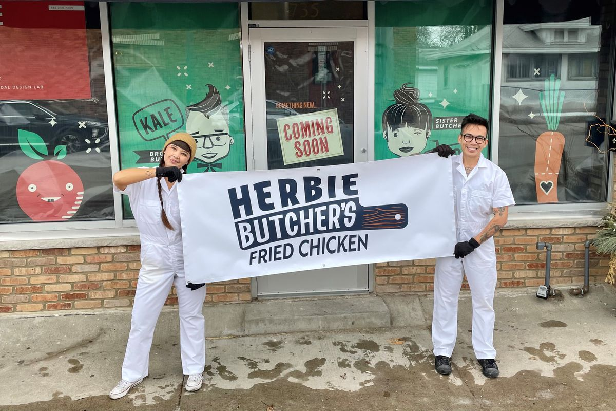 """Aubry and Kale hold a white with black print banner, """"Herbie's Fried Chicken,"""" in front of the new storefront, decorated with aqua green paper sporting cartoon versions of the Walch siblings"""