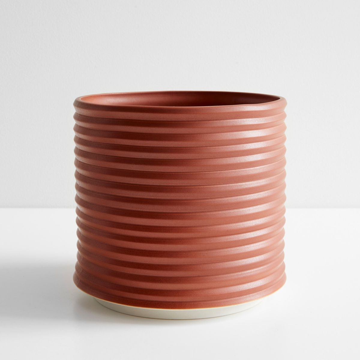 This light red, round planter is textured so that it looks like rings stacked on top of each other.