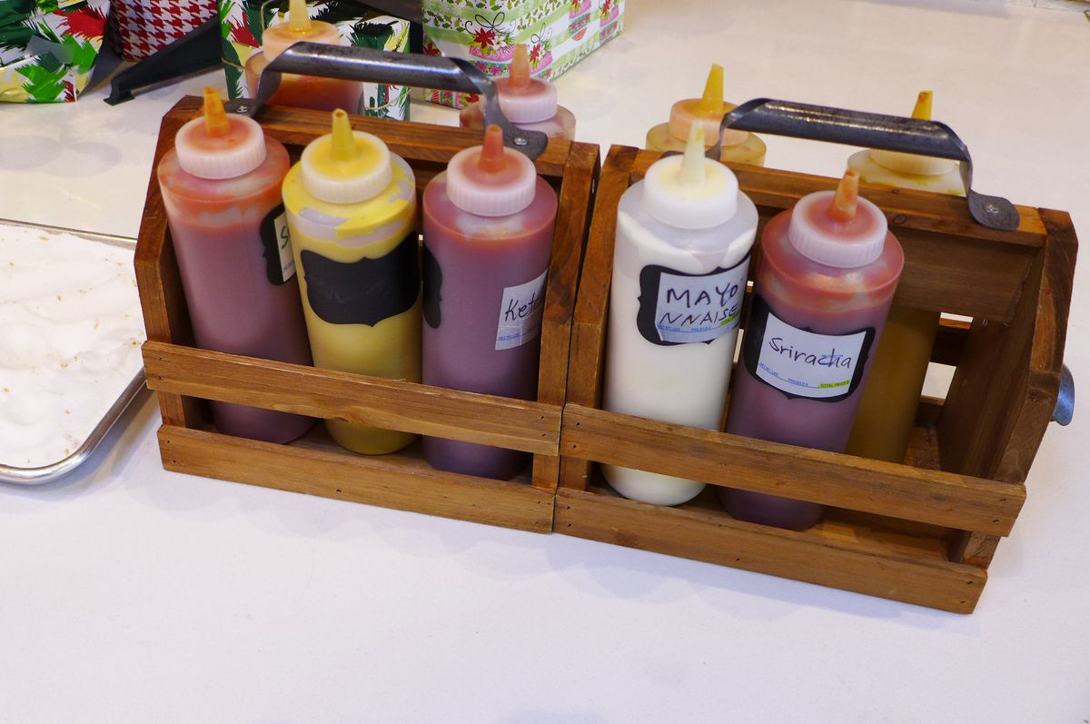 Squeeze bottles in a portable rack hold liquid condiments.