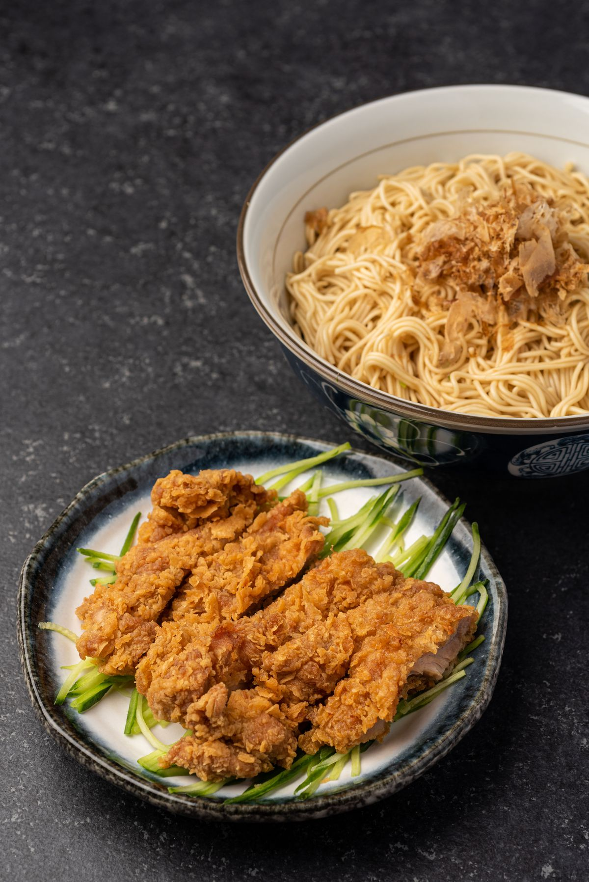 Fried chicken thighs on a table with a far bowl of noodles.