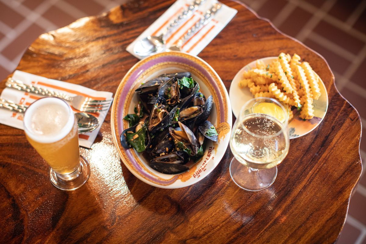 A wooden table that has a plate of mussels on it with curly fries on another plate and a tall glass of beer.