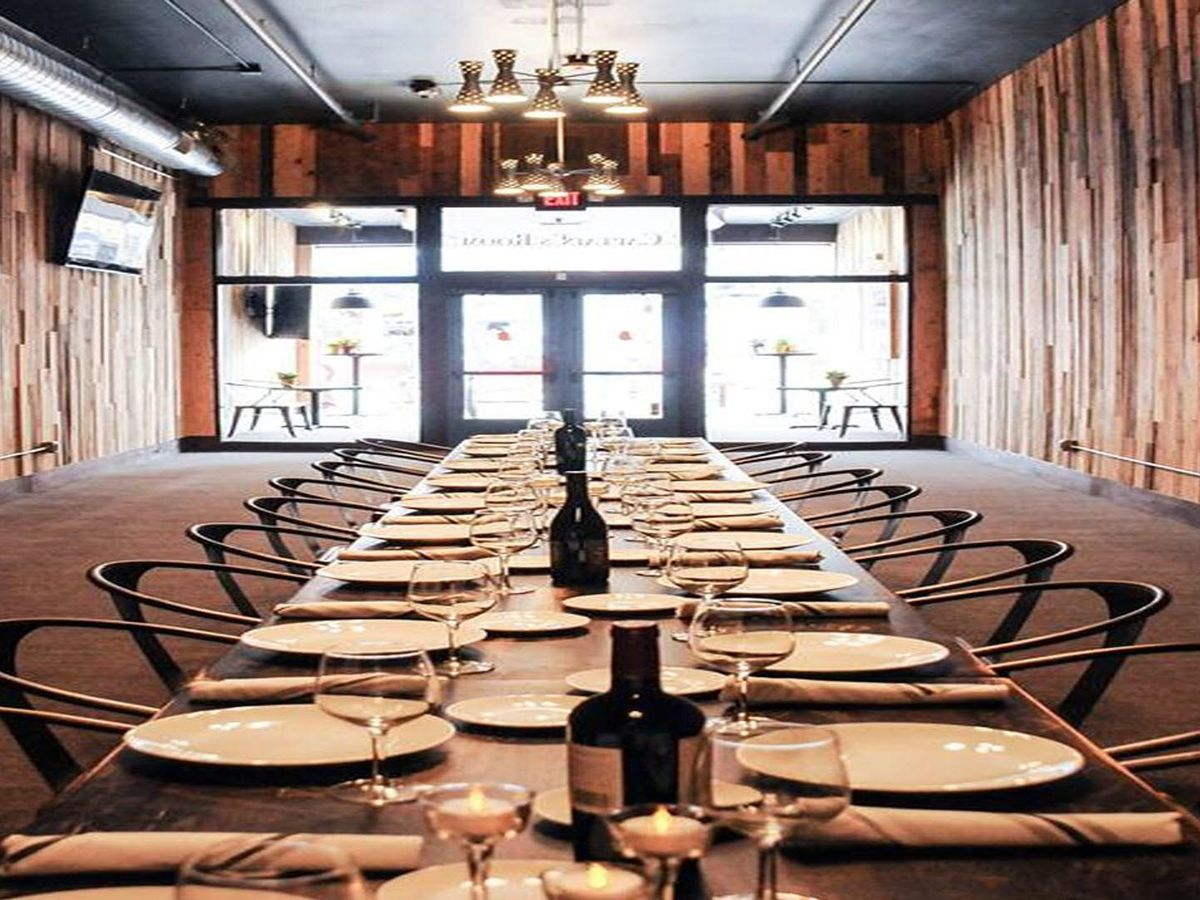 An extremely long table in a room with natural wood paneled walls.