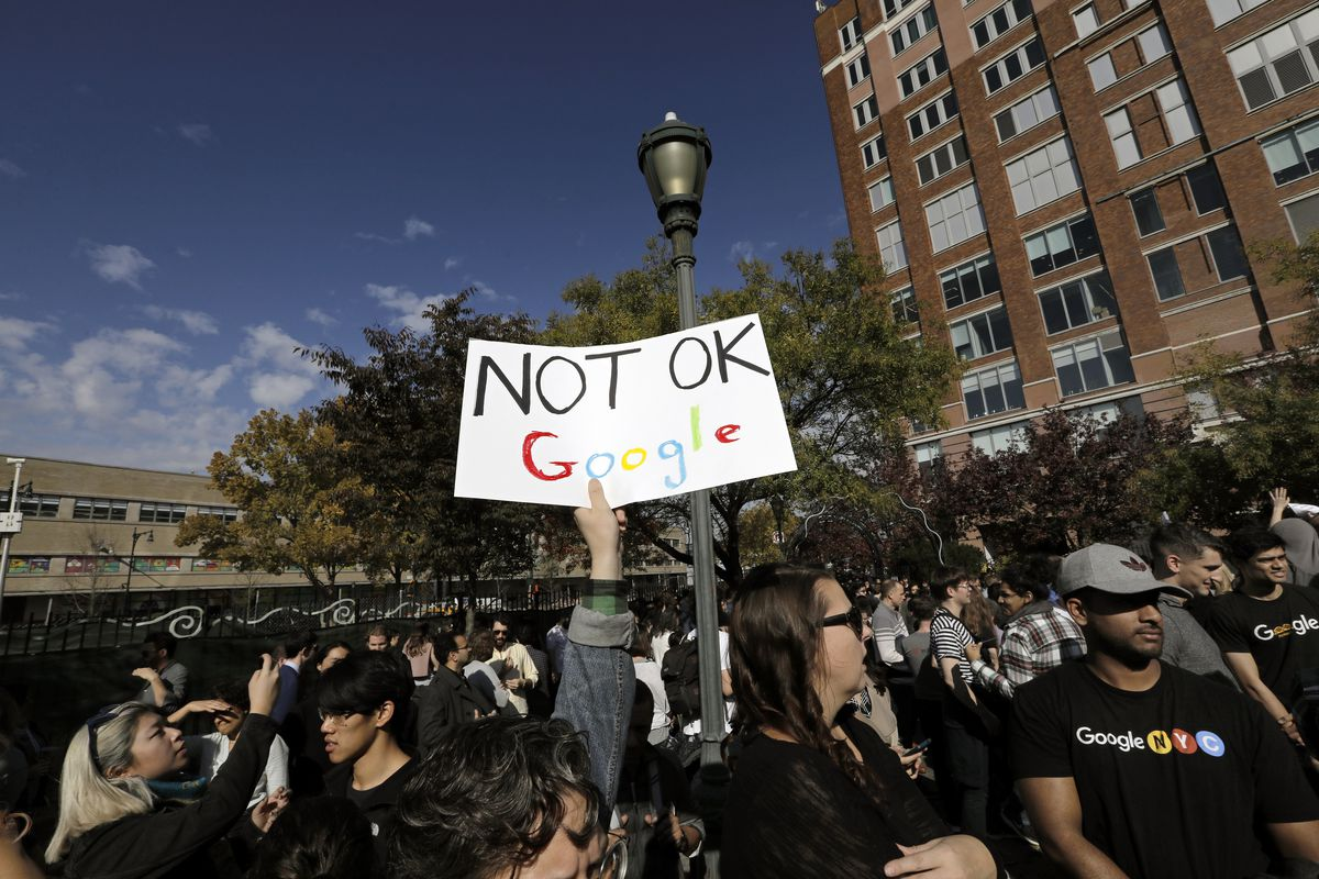 """A protester in a crowd holds a sign over their head that reads, """"Not OK, Google."""""""