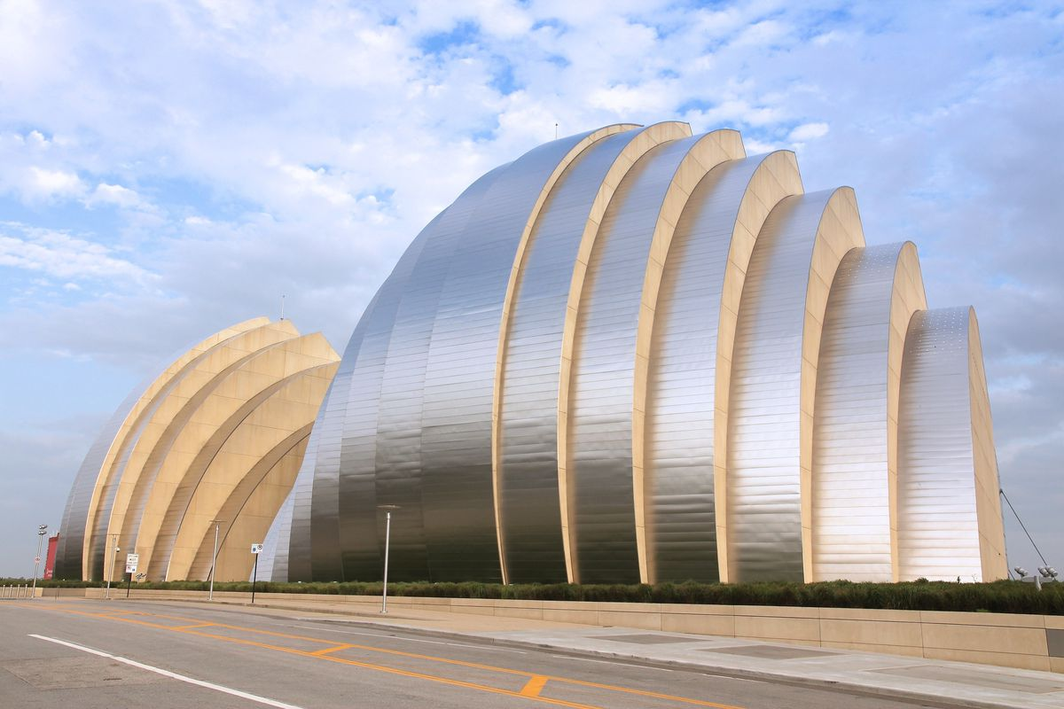 The exterior of the Kauffman Center for the Performing Arts in Missouri. The facade is stainless steel panels that are curved into a shell shape.
