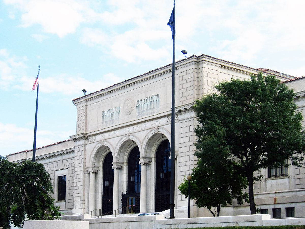 The exterior of the Detroit Institute of the Arts. The building has a white brick facade with columns. There are two flagpoles in front of the building with flags.
