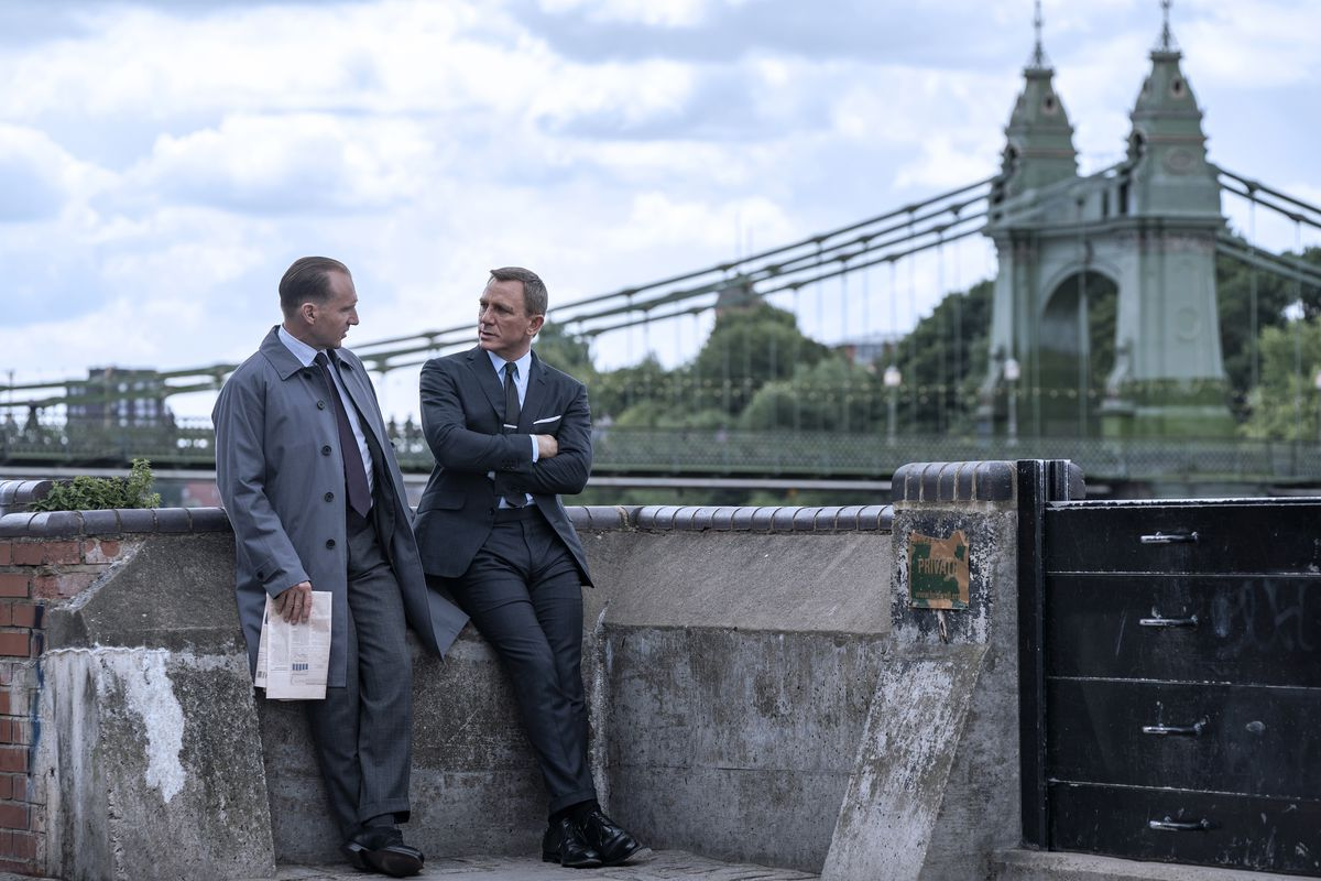 Daniel Craig as James Bond and Ralph Fiennes as M enjoy a leisurely outdoor meeting near a bridge in No Time To Die