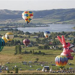 """Balloons take off during the Ogden Valley Balloon Festival over Weber County on Friday. The 15th annual event in Eden runs through Sunday. Each evening at the festival field there will be a live concert with BBQ dinner offered for purchase. The popular """"Balloon Glow"""" will take place Saturday evening at dusk."""