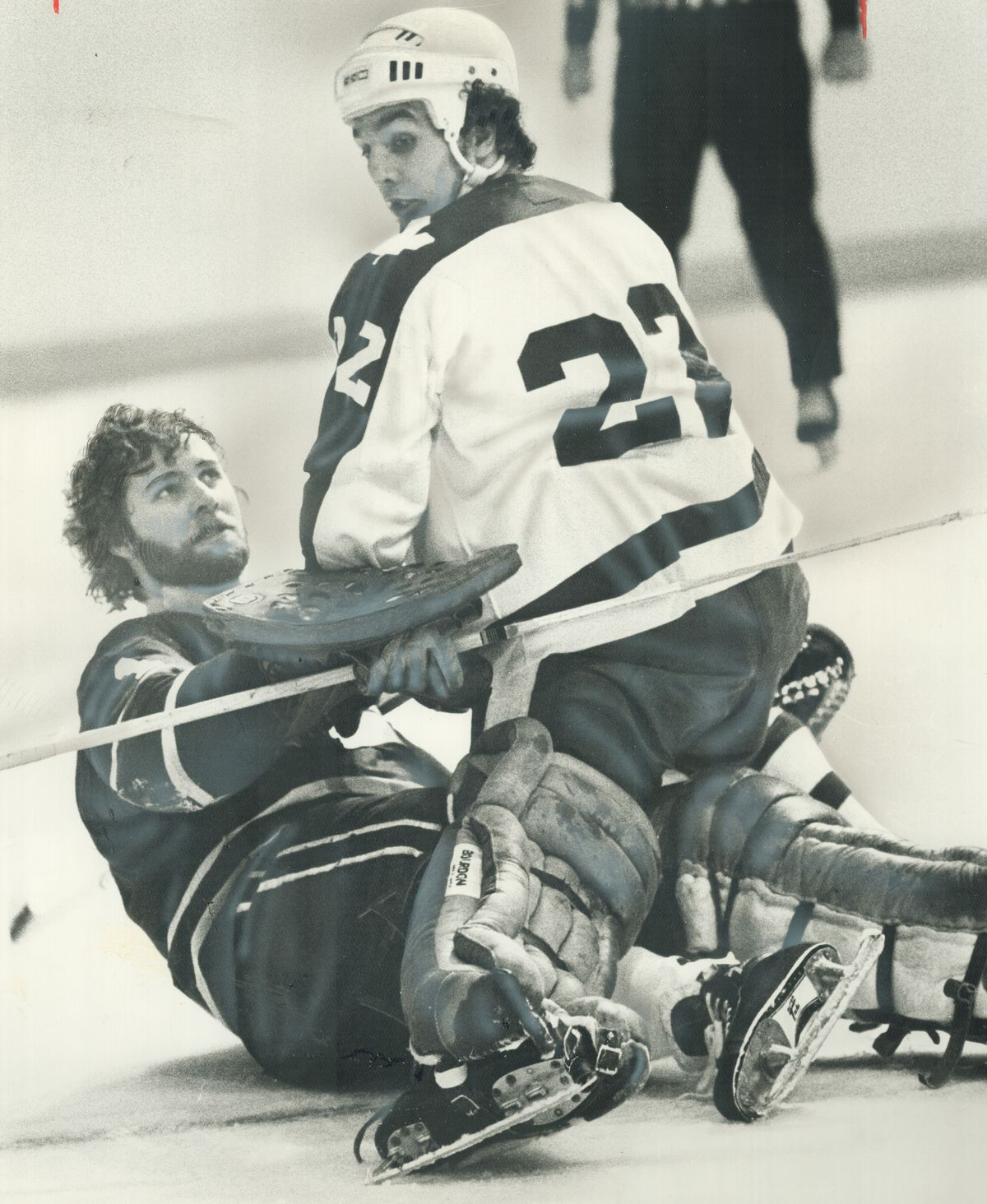 Mask Knocked Off by collision; Vancouver Canucks' goalie Gary Smith looks up at Tiger Williams of Le