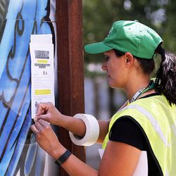 Susan Collier, of Salt Lake City Community Emergency Response Teams, posts a sign in Salt Lake City on Monday, July 18, 2016, warning of possible toxic algae contamination in the Jordan River.