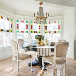 Restored original stained-glass windows bring dramatic color and sunlight into the dining area. Gold and brass accents are repeated throughout the interior, here in the chandelier and in the bar area to the right. <em>Dining table and chairs: </em><a class=