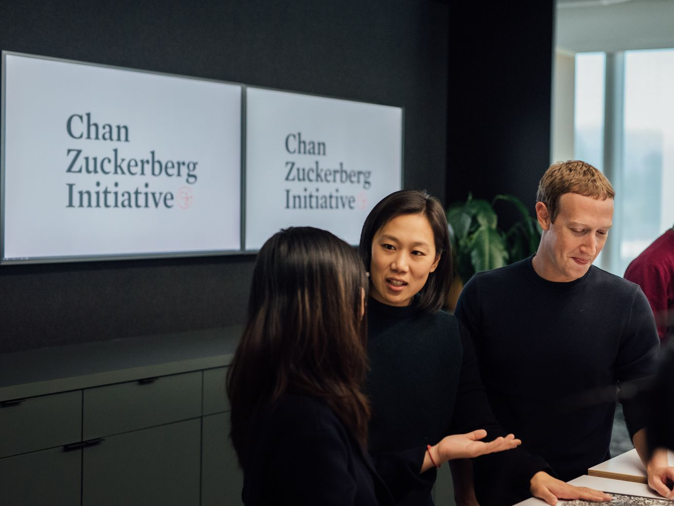 "Priscilla Chan and Mark Zuckerberg speak with another person in front of a sign reading, ""Chan Zuckerberg Initiative."""
