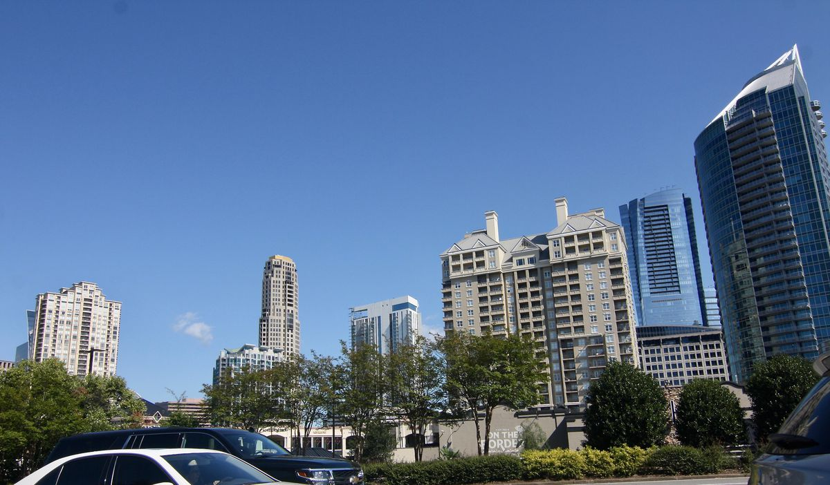 A row of tall buildings with parking lots and cars in the foreground.