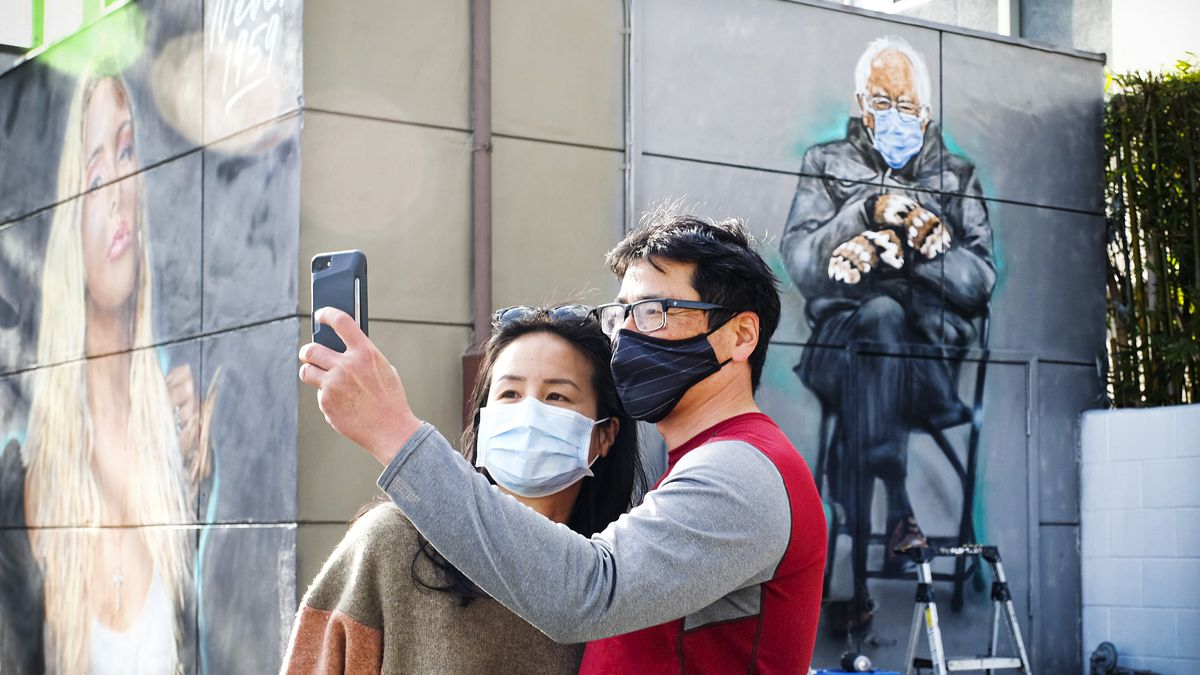 Two people taking a selfie in front of a mural of Sen. Bernie Sanders.