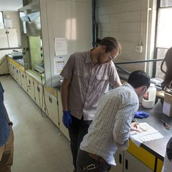Recent University of Utah graduate Tom Folke, left, U. student Simone Longo, professor Taylor Sparks and U. student Logan Kiefer examine a decal as the blue tint fades in and out with the electrical current in the Chemical and Mechanical Engineering Building on the U. campus in Salt Lake City on Thursday, June 1, 2017. They are trying to develop a technique to create windows that are able to dim electrochemically, either by remote control or in response to changing light conditions.