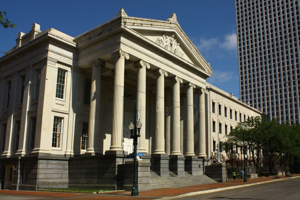 The exterior of Gallier Hall in New Orleans. The facade is ivory with columns in front of the entrance area.