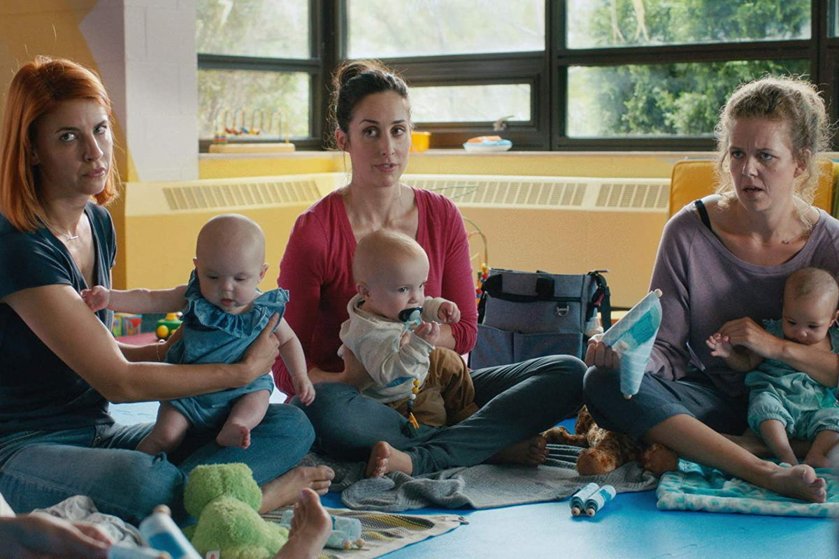 Three moms and their babies in a scene from Workin' Moms, which is streaming on Netflix.