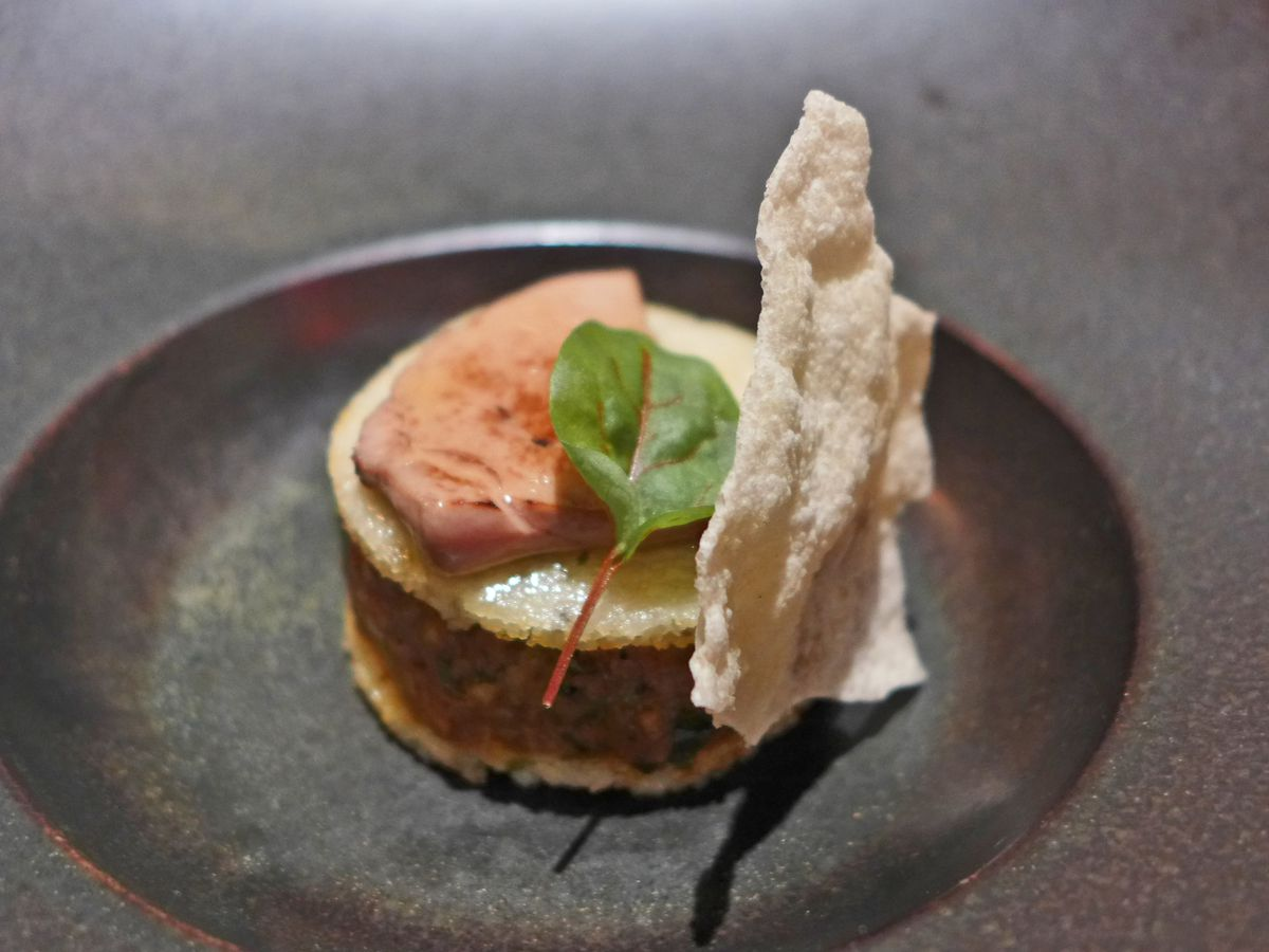 Two wafers with a filling between them, garnished with foie gras and an amaranth leaf.