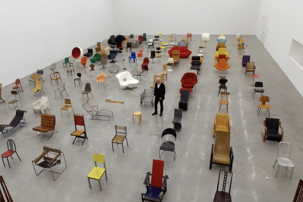 A man stands among a sea of different kinds of chairs.