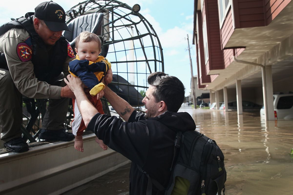 Michael Boyd passes his son Skylar over to a rescue worker as they are evacuated on an airboat from their apartment complex after it was inundated with water following Hurricane Harvey on August 30, 2017 in Houston, Texas. It was Skylar's first birthday.