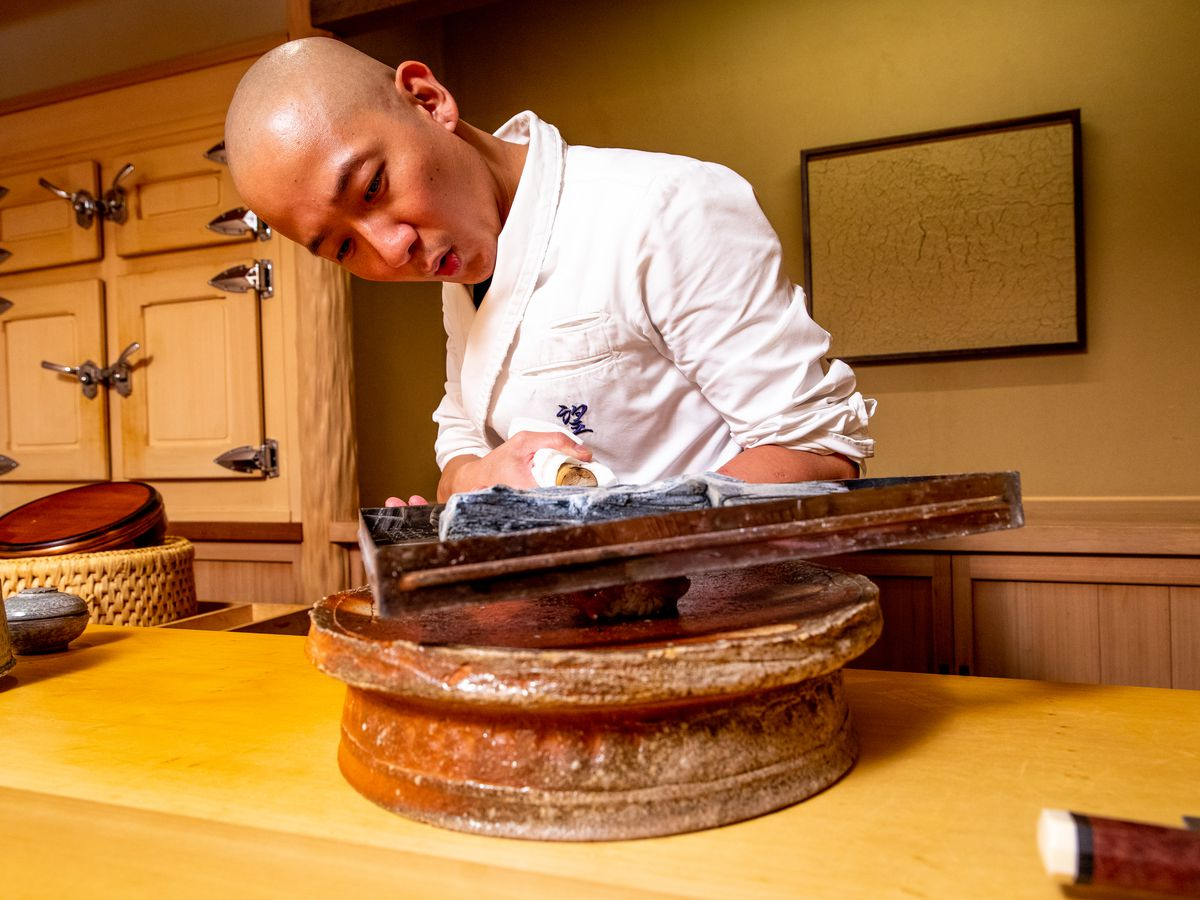 Chef Nozomu Abe holds a small box filled with binchotan charcoal above slices of tuna to grill them