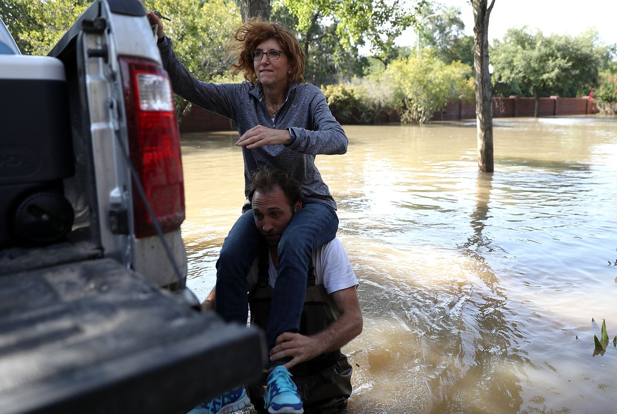 Chris Ginter carries Mila Milo on his shoulders through floodwaters as she visits her parents' flooded home on September 6, 2017, in Houston, Texas, in the wake of Hurricane Harvey.