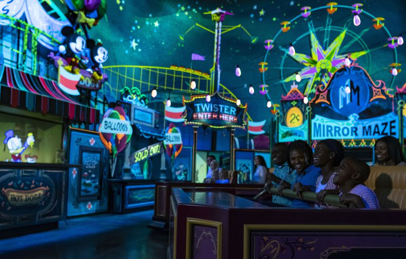 Guests visit an action-packed carnival as part of their journey aboard Mickey & Minnie's Runaway Railway