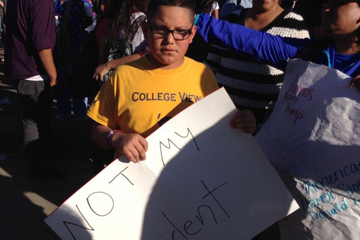 A Denver student holds a sign at a walkout to protest Trump.