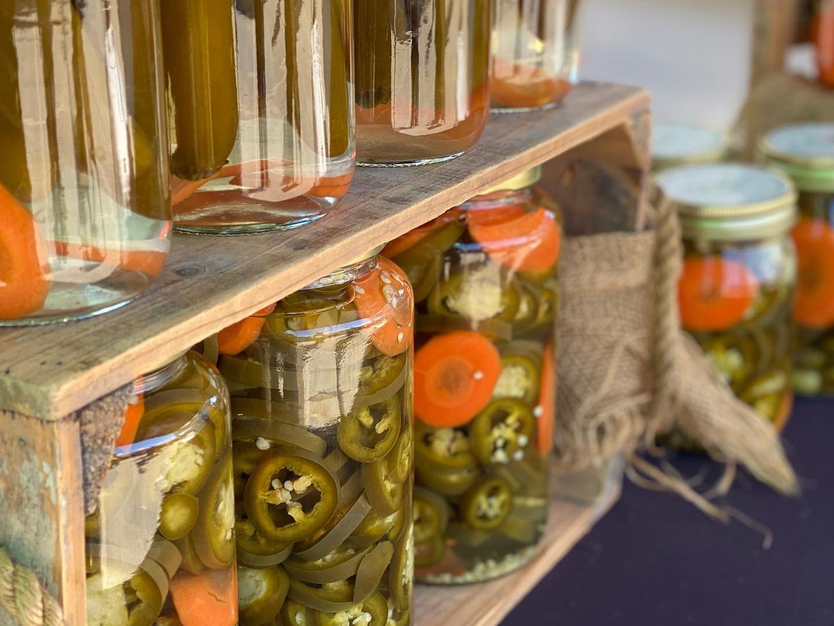 Jars of pickled jalapeños and carrots for sale at a farmer's market