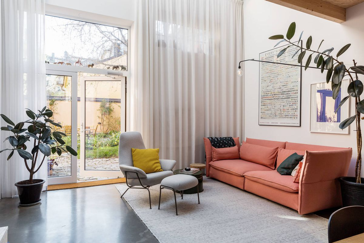 Living room featuring large windows and salmon colored couch.