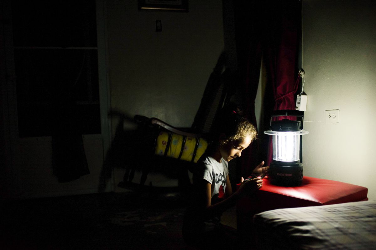 June 6: Andrea Liz Rosario Cotte, a first-grader at Paso Palmas, plays before bedtime by the light of a lantern. Her family remains without electricity and water nine months after Hurricane María hit Puerto Rico. Read More. (Rebecca Kiger)