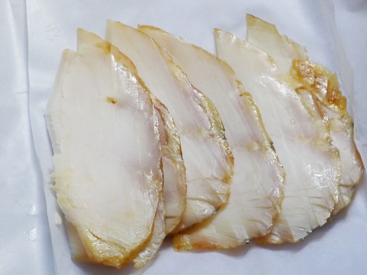 Pale slices of fish fanned on white butcher paper.