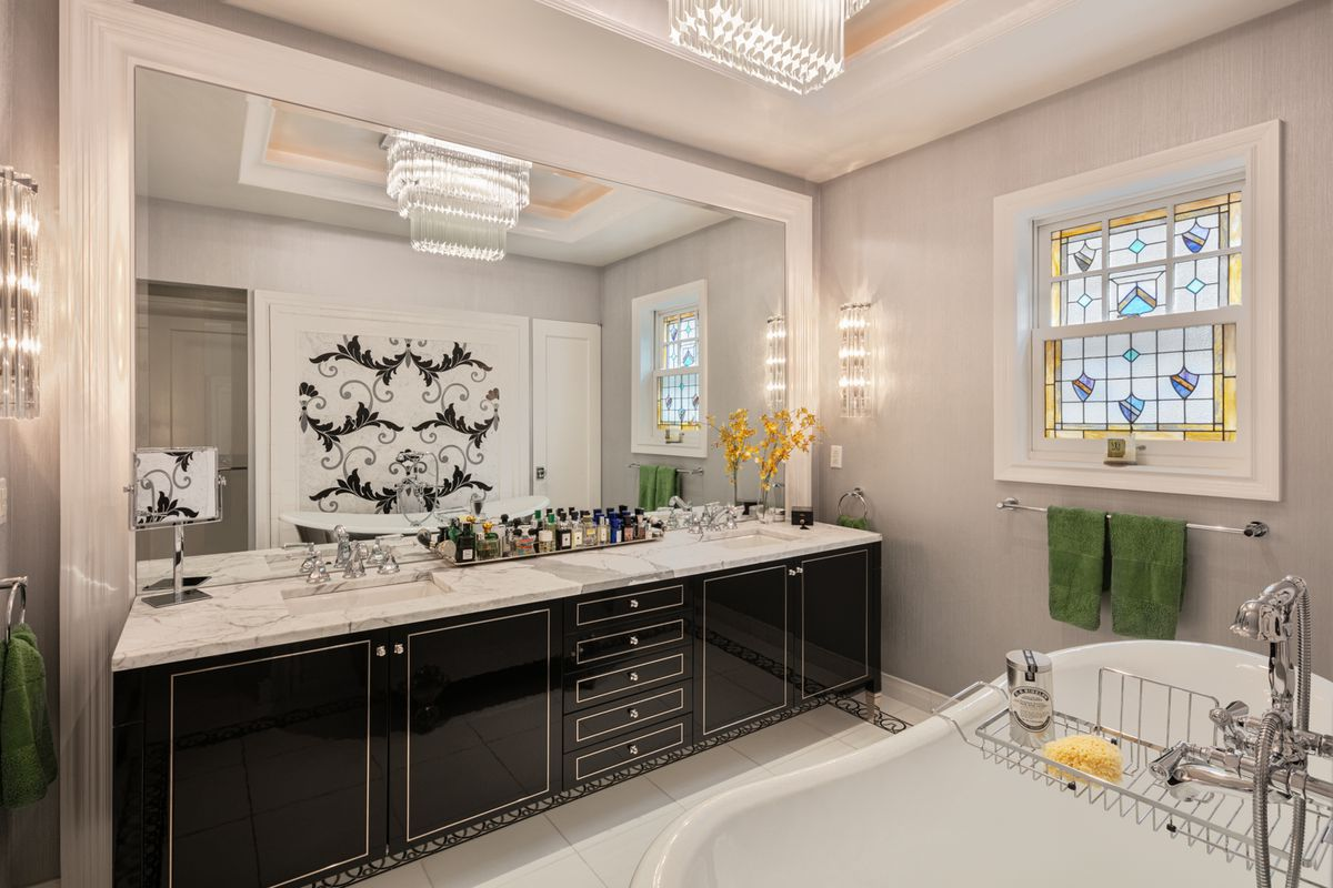 A bathroom with a small and colorful stained glass window, a large mirror, and a tub.